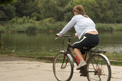 Young woman riding with bike. Young woman riding in the park biking Stock Image