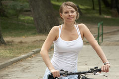 Young woman riding with bike. Young woman riding in the park biking Royalty Free Stock Photo