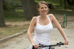Young woman riding with bike. Young woman riding in the park biking Royalty Free Stock Images