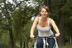 Young woman riding with bike. Young woman riding in the park biking Royalty Free Stock Photos