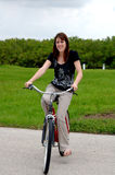 Young woman riding a bike. A pretty young woman riding a bike outdoors stock image