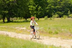 Young woman riding a bike on country road Stock Photo