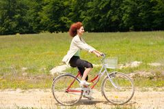 Young woman riding a bike on country road. Young woman riding a bike on a country road through forest and meadows Stock Photography