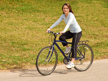 Young woman riding a bike outdoor Stock Image