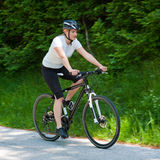 Young woman riding a bike on road through forest Royalty Free Stock Photos