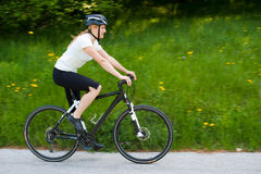Young woman riding a bike on road through forest. Downhill Stock Image