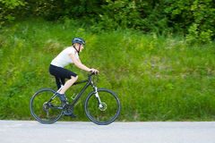 Young woman riding a bike on road through forest. In early summer morning Royalty Free Stock Image