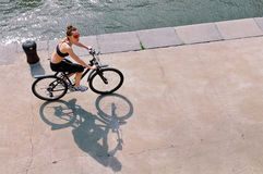 Young woman riding a bike on the stone embankment of the river Stock Photography