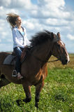 Young woman riding on a brown horse. In a field in summer Stock Photos