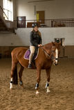 Young woman riding brown horse in indoor manege Royalty Free Stock Photography