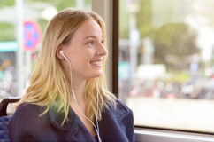 Young woman riding in a bus listening to music. Young attractive blond woman riding in a bus listening to music on earplugs smiling happily as she is looking Royalty Free Stock Photo