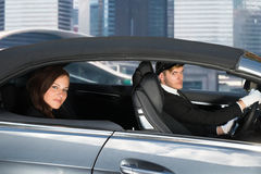 Young Woman Riding In A Car With Chauffeur Royalty Free Stock Image