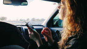 A young woman is riding in the car in the passenger seat. In her hand holds a mobile phone. Traveling to cars, good stock video