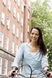 A young woman riding her bicycle in the street Stock Photography
