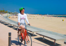 Young woman riding her bike. Along the beach in Barcelona Royalty Free Stock Image