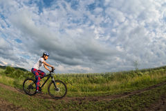 Young woman riding her bike on a rural trail Royalty Free Stock Photo