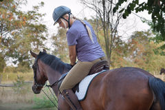 Young woman riding horse. Happy young woman riding horse Royalty Free Stock Photography