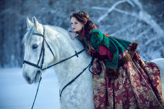 Young woman riding a horse. Young woman in a fabulous way of riding on a white horse Royalty Free Stock Photo