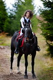 Young woman riding horse outdoor Royalty Free Stock Image