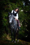 Young woman riding horse outdoor Stock Photo