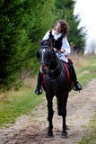 Young woman riding horse outdoor Stock Image
