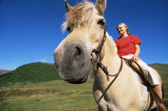 Young woman riding horse in rural setting Royalty Free Stock Photo