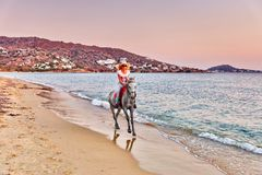 Young woman riding a horse. At sunset on the beach of Plaka in Naxos island, Greece Stock Images