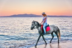 Young woman riding a horse. At sunset on the beach of Plaka in Naxos island, Greece Royalty Free Stock Photography