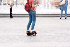 Young woman riding a hoverboard on the city square. New movement and transport technologies. Close up of dual wheel self Royalty Free Stock Photography