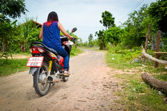 Young woman riding a motorcycle. Young asian girl riding a 125cc motorcycle on a narrow dirt road Royalty Free Stock Images