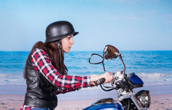 Young Woman Riding Motorcycle Past Beach Royalty Free Stock Photography