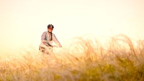 Young Woman Riding Mountain Bikes in the Beautiful Field of Feather Grass at Sunset. Adventure and Travel. stock photos