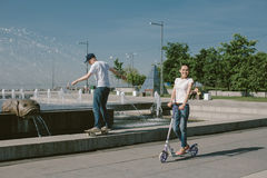 Young Woman Riding a Scooter with her Husband on a Skateboard. A Royalty Free Stock Image