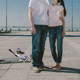 Young Woman Riding a Scooter with her Husband on a Skateboard. A Stock Photo
