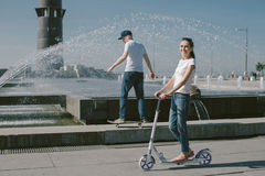 Young Woman Riding a Scooter with her Husband on a Skateboard. A Royalty Free Stock Photo