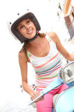 Young woman riding scooter Stock Images