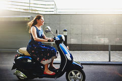 Young woman riding the scooter Royalty Free Stock Images