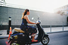 Young woman riding the scooter Royalty Free Stock Image