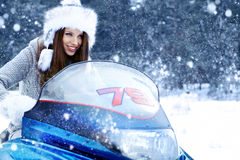 Young woman riding a snowmobile Royalty Free Stock Image