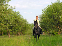 Young woman riding in the summer garden Stock Image
