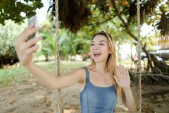 Young woman riding swing and making selfie by smartphone, sand and trees in background. royalty free stock images