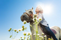 Young woman riding white horse in sunny summer day Stock Photo