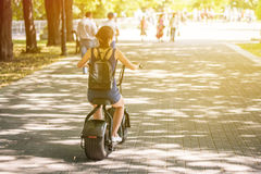 A young woman riding zero-emission eco electric scooter bike  in a city park. Back view. Day, sunlight Stock Photo