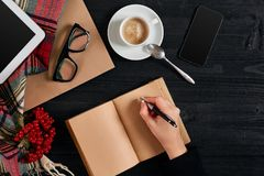 Young woman right hand writing on blank notebook on wood table with coffee cup, smartphone, and glasses beside in Royalty Free Stock Image
