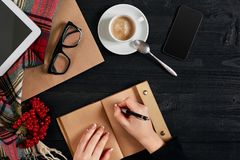 Young woman right hand writing on blank notebook on wood table with coffee cup, smartphone, and glasses beside in Royalty Free Stock Images