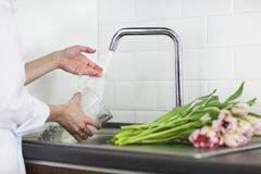 Young woman rinsing and cutting flowers and pouring water into  Royalty Free Stock Image