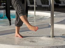 Young woman rinsing of the feet at the pool. On a hot day in Puerto Rico, Gran Canaria Stock Image