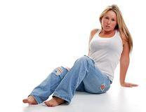 Young woman with ripped jeans sitting down royalty free stock photography