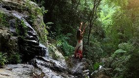Young woman rises hands at waterfall in jungle Koh