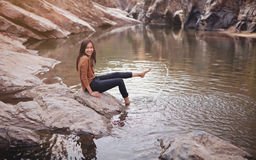 Young woman on a river bank playing with water Stock Photography